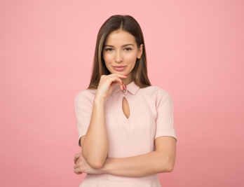Attractive woman wearing a tunic top on a pink background