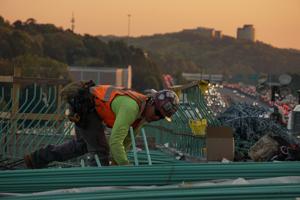 Builder wearing printed high vis vest on a roof